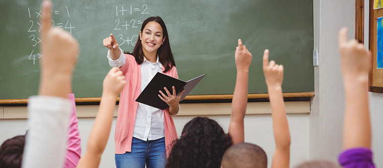 Adequate Staff at school pictured by teacher in front of classroom full of students