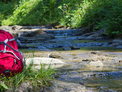 Backpack next to a creek on a hiking trail