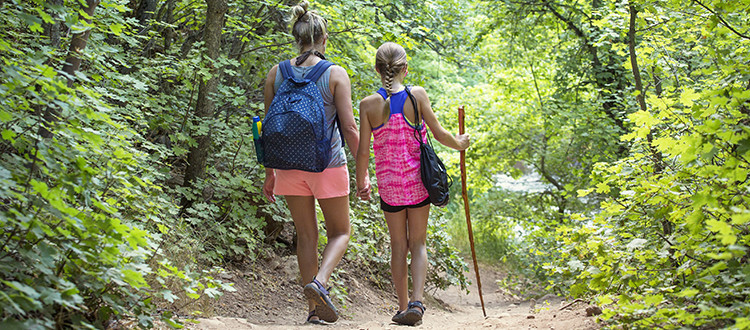 Mother And Daughter Walk Along Hiking Trails